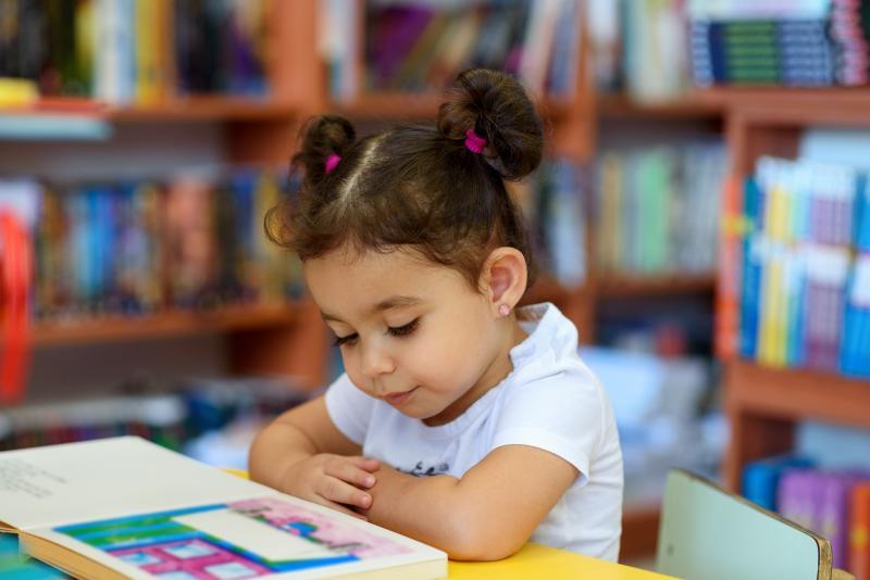 Hispanic Child Reading in Library