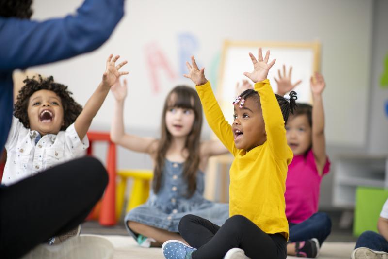 Kids with Hands Up in Classroom