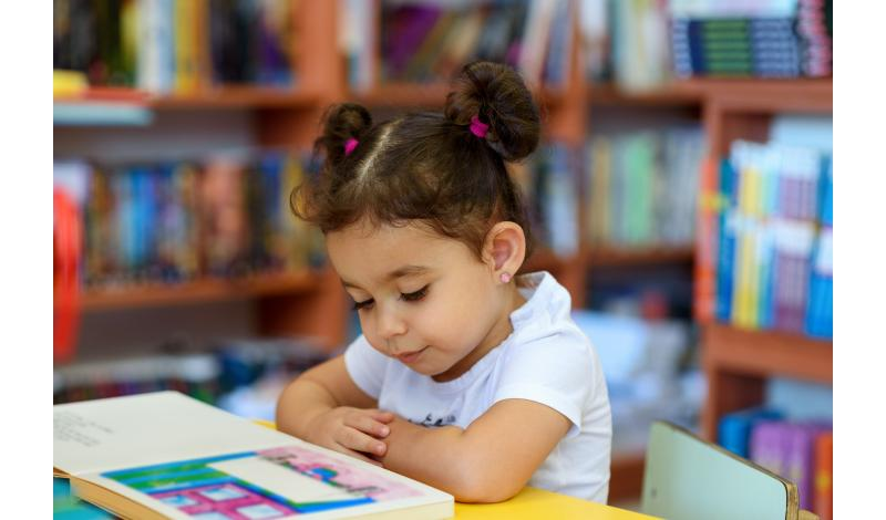 Hispanic Child Reading in Library