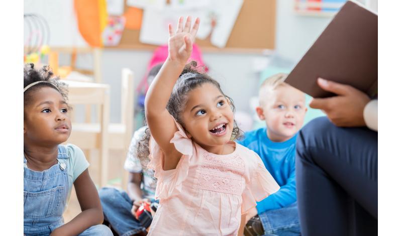 Little Girl Raising Hand in Classroom