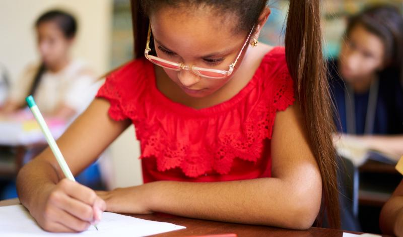 Young Girl Writing at Desk